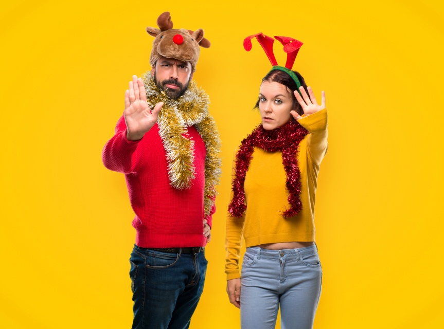 Couple dressed up for the christmas holidays making stop gesture with her hand denying a situation that thinks wrong